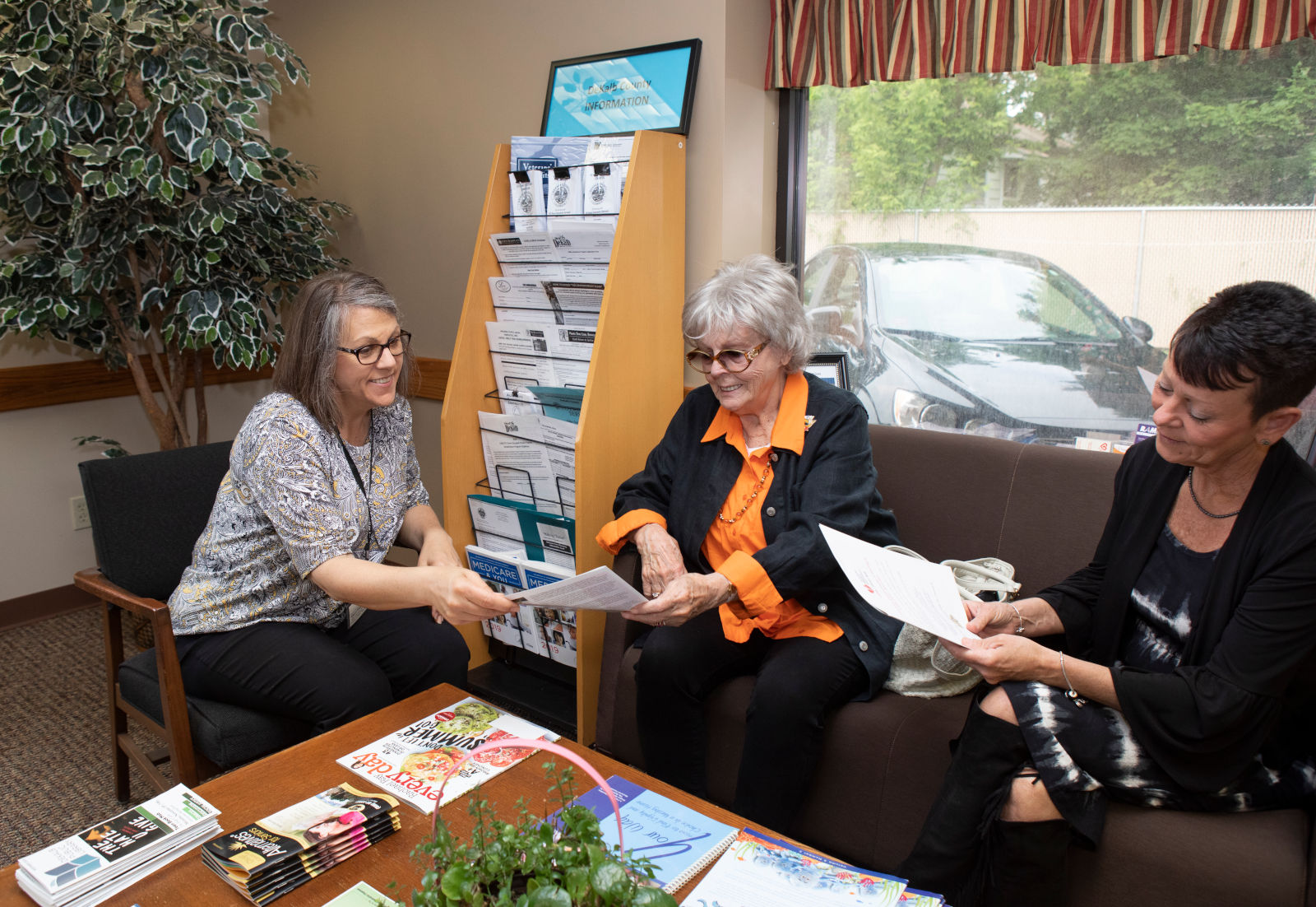 Elder Care Services Employees provide information to an older woman